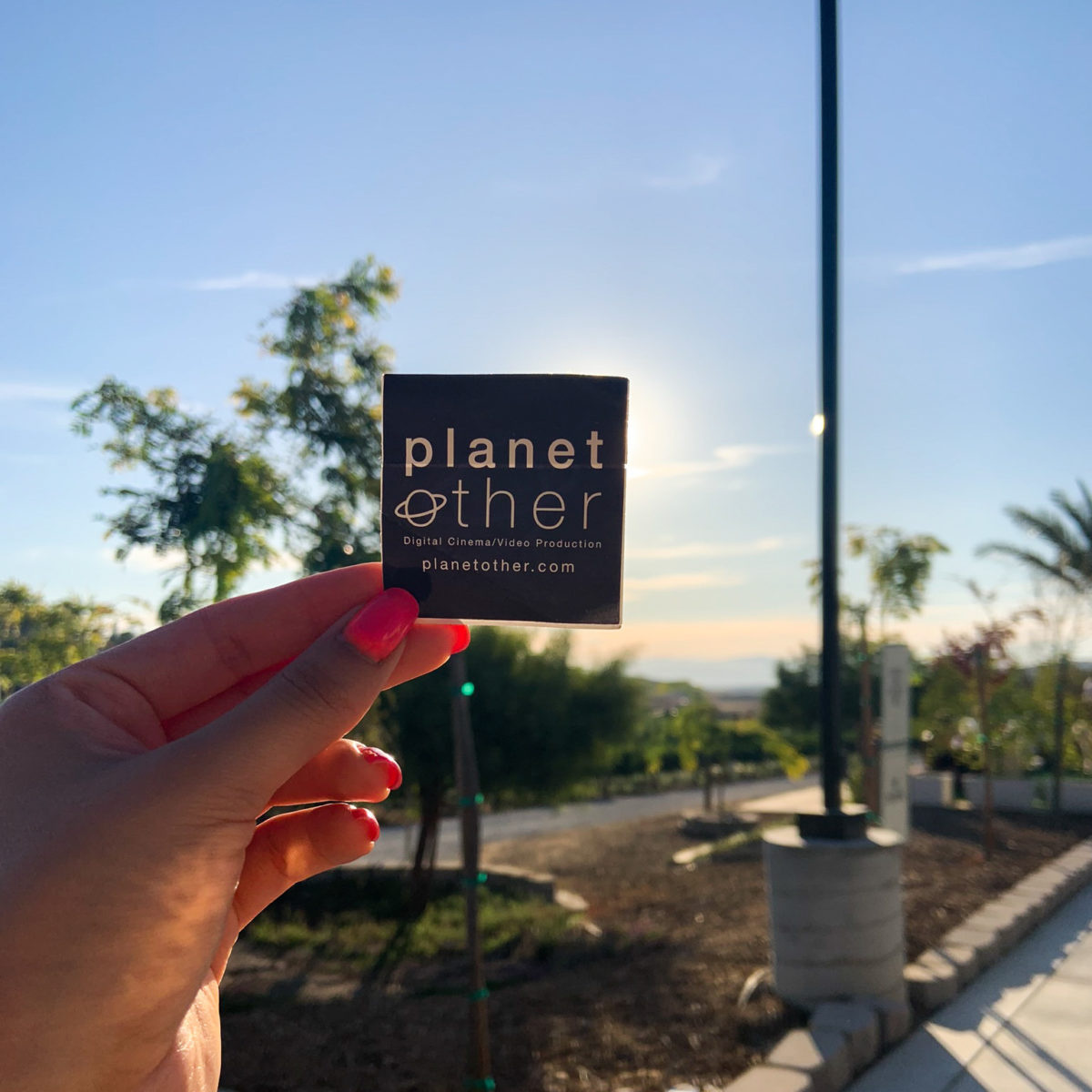 female hand holding PlanetOther sticker