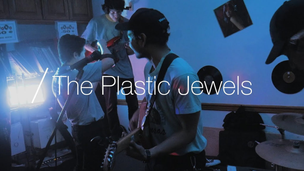 rock band playing music, text in fore-ground - The Plastic Jewels