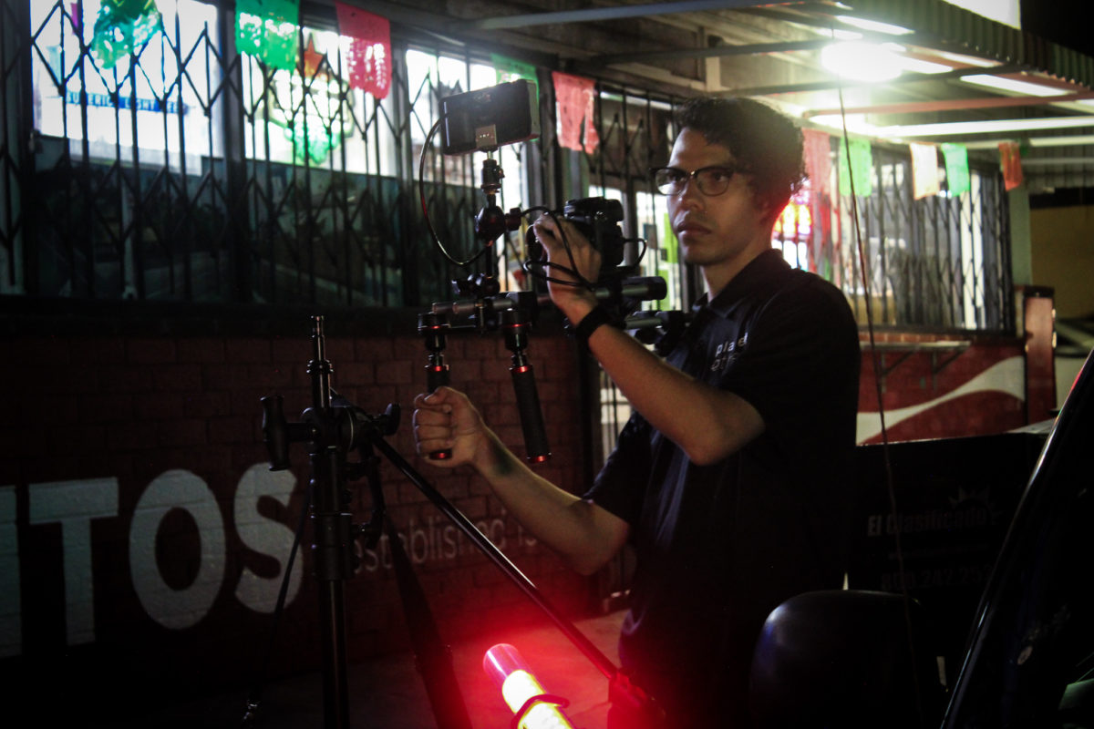 Juan Abad filming in front of store